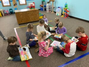 Photo of children ages 2 through 5 in the Sprouts room reading their bibles